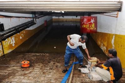 工作人员使用工具,汲取地下停车场的积水。