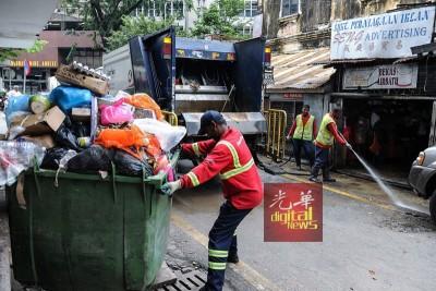 工作人员清理堆积在水灾区路面的垃圾。