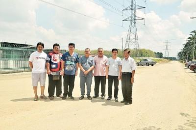 黄镇津向前来巡视的行动党甲抛峇底区联委会及平安村北部社委会一行人解释当地路况,右3为赖国平。