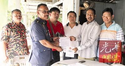 沙希淡(右2)移交浮罗新路峰港口义务消防队注册证书予涂意隆(左3),左2自扎拉、杨松兴同谢坤祥陪。