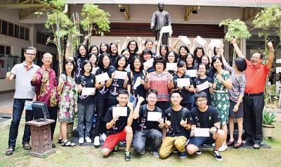林丽芳(前排左8)与开心地出示成绩单的优秀考生一起合影。