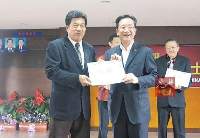 卓双才(左)接领黄惠康的资助金。