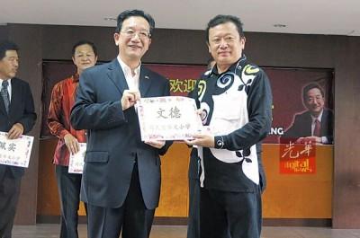 王孙文(右)接领黄惠康的资助金。