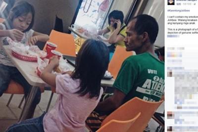 轻度中风的单亲父亲,在快餐店里看着2名小女儿吃炸鸡,自己面前却什么都没有。这张展现父爱的照片在菲国社群网站感动了13万人,民众纷纷解囊相助,政府也加码伸援。(图片来源:Jhunnel Sarajan脸书)