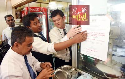 卫生局官员在王耶宗(右)的陪同下,在环境卫生不合格的食肆中,贴上关闭两周的通告。