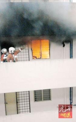 消拯员进入正在燃烧的组屋单位房间,进行灭火工作。