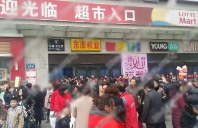 有民众在被查封的乐天玛特超市门外拍照。