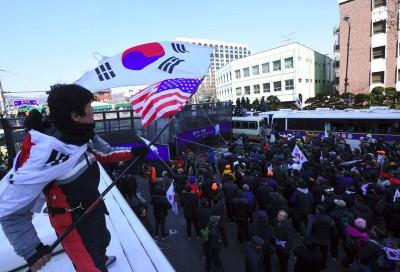 支持朴槿惠的民众与警员冲突,有示威者站在警方巴士顶部抗议。(法新社照片)