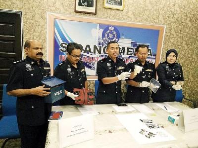 哈林(中)与警官展示所起获的干案工具及赃物。