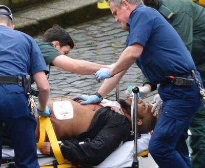 持刀袭警嫌犯被送上救护车。