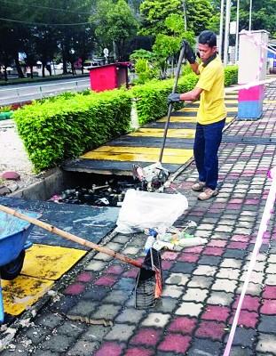 槟岛市政厅清洁工人忙着扫垃圾。