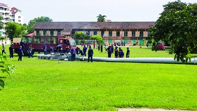 执法人员进场拆除西日落洞国民中小学草场上的电讯塔。