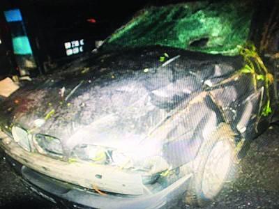 失控翻覆的轿车,严重撞毁。