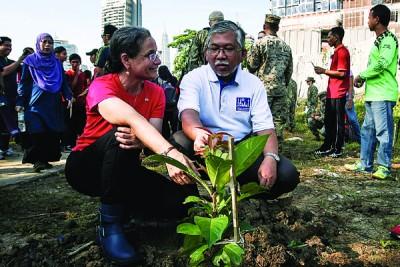 那吉(右)与拉赫第一同栽种树木,爱护环境。