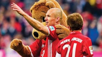 拜仁的进球功臣罗本(中)赛后与拜仁吉祥物柏尼一起开心庆祝球队胜利。