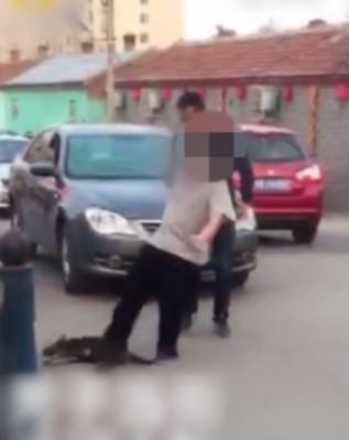 男子用脚踢小狗。