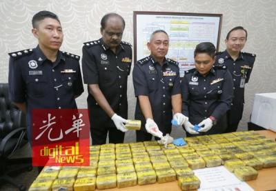 霹雳代总警长拿督哈斯南(中)在拉威(左2)的陪同下,展示起获的马丸毒品。左1阿扎及查案官玛斯丽娜(右2)。