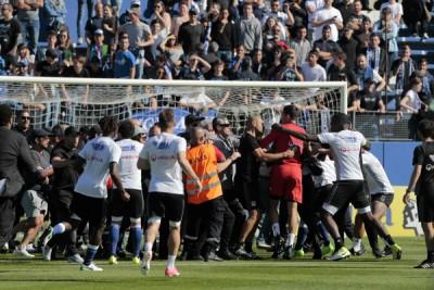 在半场结束后,巴斯蒂亚球迷冲进场内攻击里昂门将洛佩斯(红衣者)。