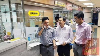 卢界燊(左)在光大3楼用柜台电话,与州秘书署官员交涉,查询申请文件程序。右起为黄志毅和李文典。