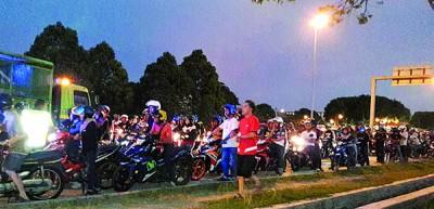 警方在外环公路设路障,检查来往的摩托车。