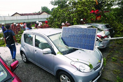 停车场内的太阳能照明灯灯柱遭大风吹倒,压及一辆停放着的汽车。