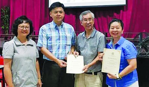 韦建华赠送纪念品予张升荣及何桂桦,左一为覃秋璇校长。