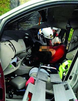 解除拯人员将司机抬出车外。