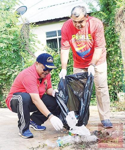 沙希淡(左)响应大扫除运动,清理地上的垃圾。右为贾菲里。