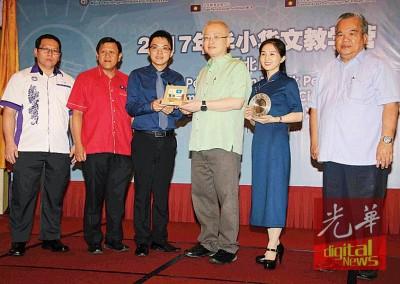 魏家祥(右3)分别赠送纪念品给张泰忠(左3)及胡红梅(右2)。左起为林贤哲、蔡励佳;右是赖明忠。
