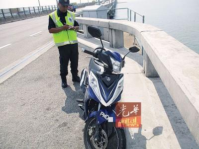 图为青年驾驶到大桥上的摩托车。