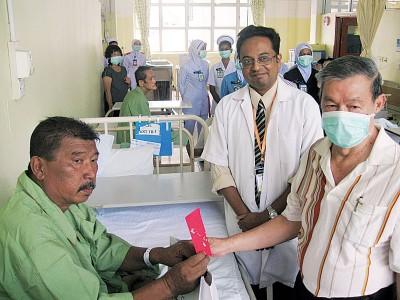 马来西亚防痨协会槟州分会主席许木贵(右)在槟城医院呼吸内科主任依法(左)陪同下,分发红包予贫穷病患。