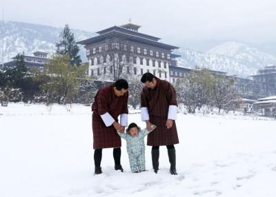 小王子(中)手牵着父王和祖父的手,在雪地上散步,场面温馨。