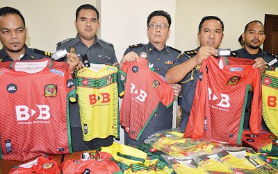 山苏尼占(右2)与一众执法官员示出当局所充公的冒牌球衣。