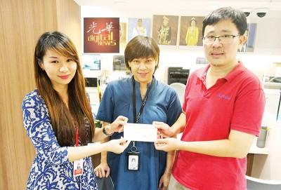 周慧妮(左)在林嘉嘉(中)见证下,移交5万令吉支票予涂智得(右)。