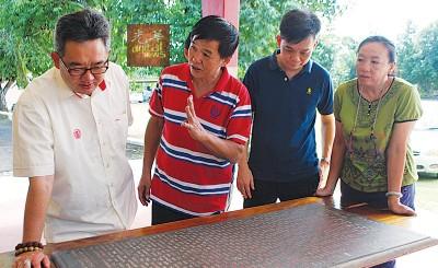 吴志刚(左2)在董事和家长陪同下,向蔡通易(左1)汇报记录校史的牌匾。