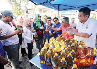 民众耐心排队等候领取免费食油,右1为方志伟、再迪、阿布峇加、陈奂维。