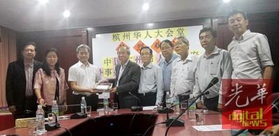 马满鹤(左3)移交纪念品予许廷炎(左4),由于戴金荣(左起)、陈洁、陈坤海、梁伟宏、骆保林、郑汉荣和王健大陪同。