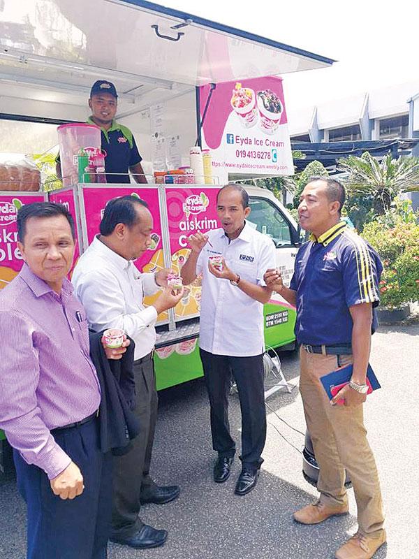 赛卡马汝丁与法力品尝现场流动餐车售卖的雪糕,并聆听业者介绍其创业过程。