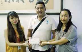 周慧妮(左)移交义款予冯淑香(右), 由潘志成见证。