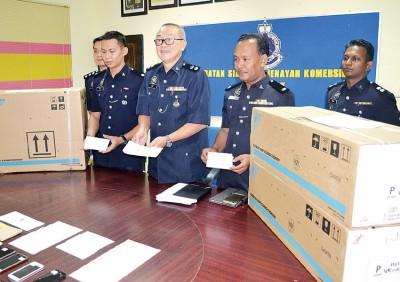 李友强警监(左2)向媒体展示无法兑现的支票及所起获的热博平台。