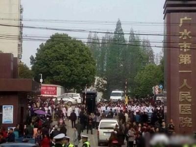 医护人员手持标语、横幅在医院门口抗议,引民众围观。
