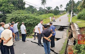 河堤坍塌事件,造成道路断成三截。振林山马华和居民在现场了解情况。