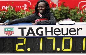 肯尼亚名将玛丽凯塔尼在列有自己创下的2小时17分42秒的世界纪录电子记录牌前开心的拍照。