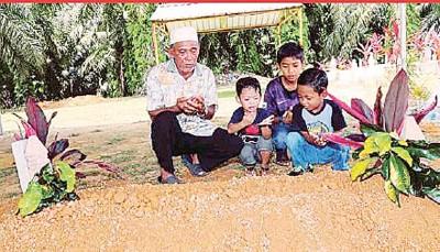 阿末莫泰(左)与其他孙子们,在塔奇阿敏坟前祈祷。