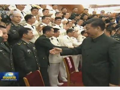 习近平与新调整组建的军级单位主官握手。