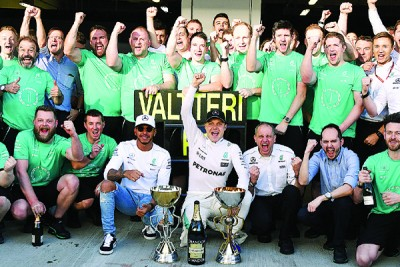 博塔斯(前排右4)赢得个人F1生涯首个冠军后与队友汉密尔顿(前排左3)及奔驰车队全体人员欣喜合照。