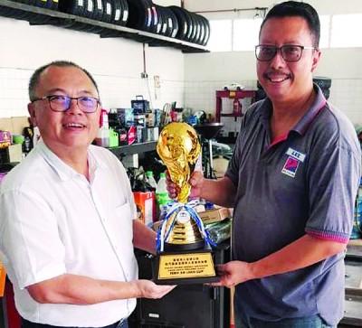 赵巧莲杯杯主陈德和(左)移交崭新常年杯予槟城华人足球公会秘书李伍辉。