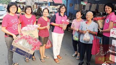 黄婉贤(右)、陈赛珍(右4)在巴刹送花庆母亲节。