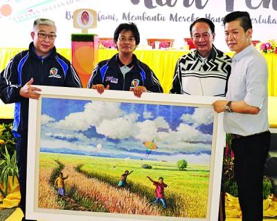 拿督林武樟(右)以1万2000令吉标得「小孩在稻田玩风筝」的油画。
