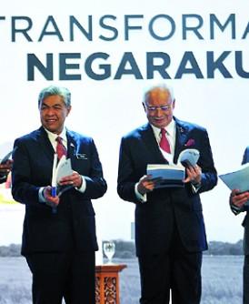 纳吉(左3)在阿里韩沙、阿末扎希及依德里斯加拉陪同下翻阅2016年国家转型计划年度报告。